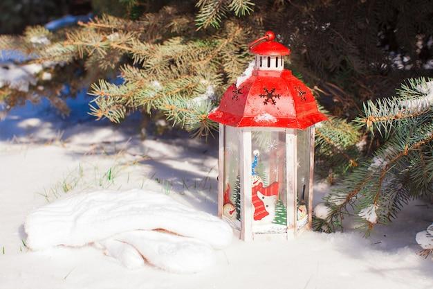 Lanterna decorativa de natal perto de ramo de abeto na neve dia de inverno