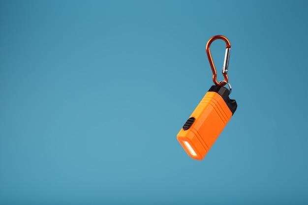 Lanterna elétrica conduzida laranja com um mosquetão em um fundo azul. luzes led em voo.