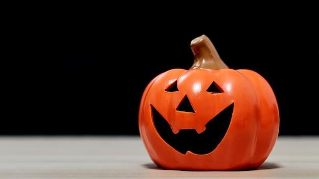 Lanterna jack o de abóbora festival de halloween na mesa de madeira em frente a um fundo escuro assustador com textura para o desenho do banner