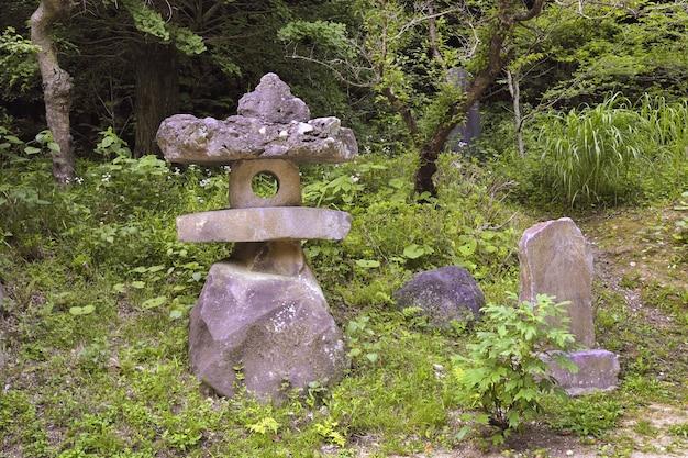 Lanterna japonesa tradicional feita de pedras vulcânicas brutas em uma floresta verde