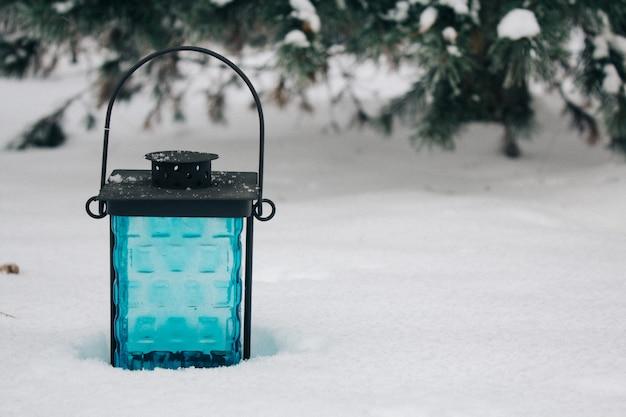 Lanterna preta e azul na neve contra ramos cobertos de neve.