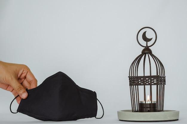 Lanterna que tem o símbolo da lua no fundo branco com uma mão segurando a máscara para proteger o vírus corona ou covid-19 para a festa muçulmana do mês sagrado do ramadã kareem.