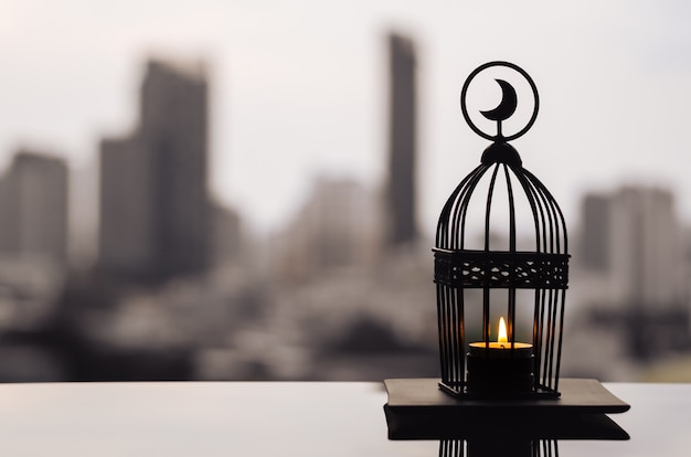 Lanterna que tem o símbolo da lua no topo com o fundo da cidade para ramadan kareem.