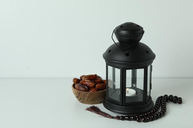 Lanterna, rosário e taça de tâmaras na superfície branca