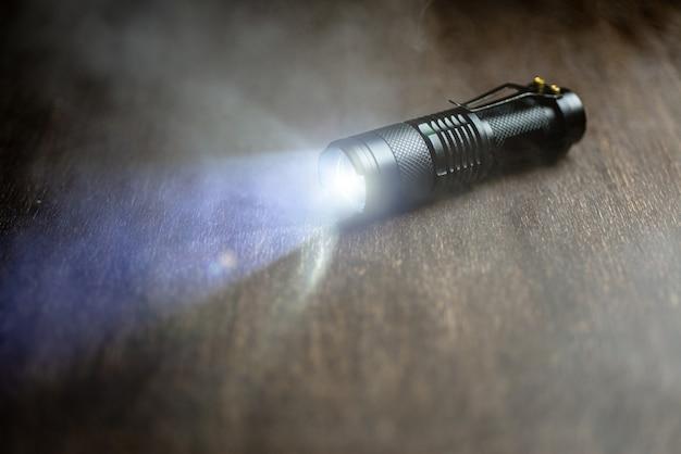 Lanterna tática à prova d'água. lanterna led brilha na mesa em forma de fumaça ..