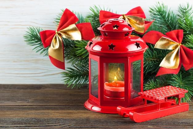 Lanterna vermelha com uma vela acesa e decoração de natal em fundo branco de madeira com árvore de natal