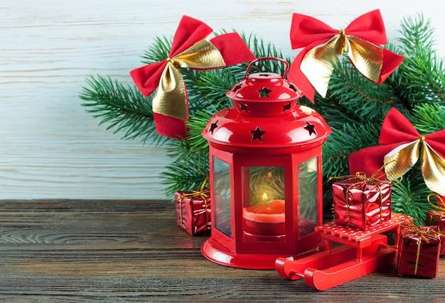 Lanterna vermelha com uma vela acesa e decoração de natal em fundo branco de madeira