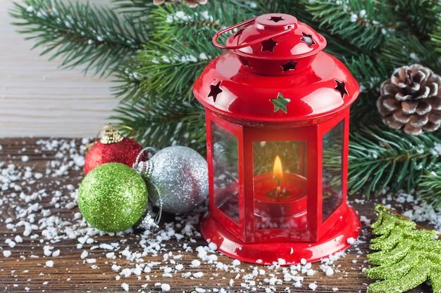 Lanterna vermelha com uma vela acesa e decoração de natal sobre neve e fundo branco de madeira