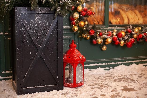 Lanterna vermelha de natal na neve com guirlanda de natal no quintal no terraço