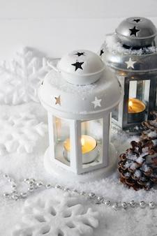 Lanternas brancas e metálicas e decoração de natal em fundo claro