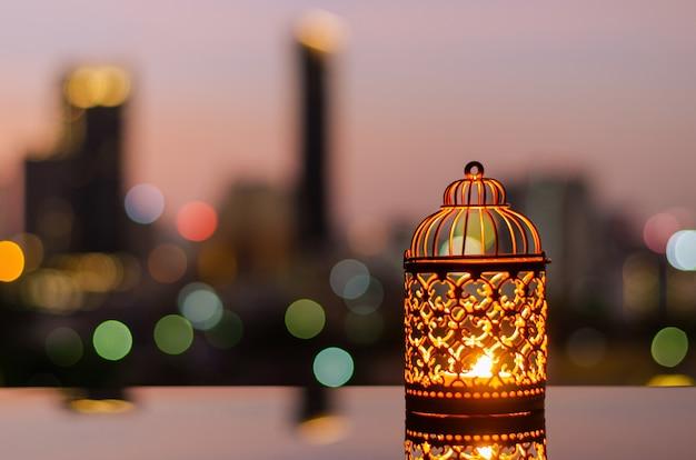 Lanternas com luz de fundo do céu do amanhecer e bokeh da cidade para ramadan kareem.
