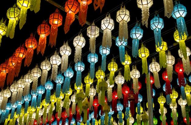 Lanternas de suspensão coloridas que iluminam-se no céu nocturno no festival de loy krathong em do norte de tailândia