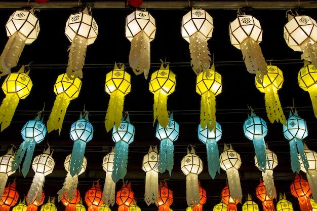 Lanternas de suspensão coloridas que iluminam-se no céu noturno no festival de loy krathong