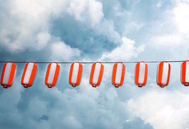 Lanternas japonesas vermelho-brancas de papel chochin que pendura no céu azul. verão