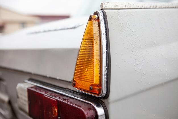Lanternas traseiras direito de um carro retro, depois da chuva