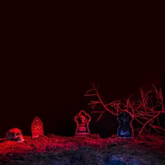 Lápides e crânio iluminados por luz vermelha no chão