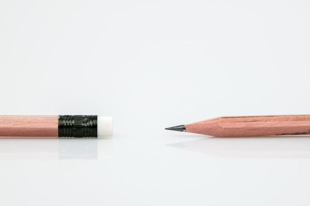 Lápis afiado contra a borracha na outra extremidade do lápis no fundo branco