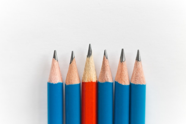 Lápis afiados simples isolados no fundo branco, vermelhos entre os azuis