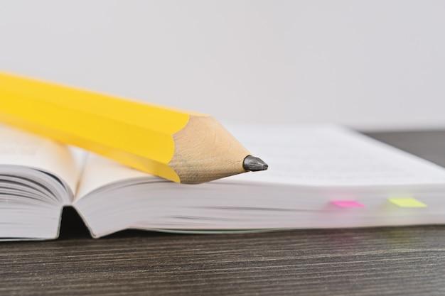 Lápis amarelo grande em um livro aberto