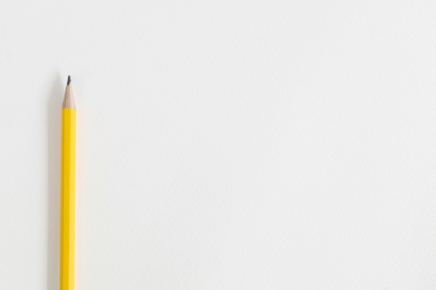 Lápis amarelo sobre papel de desenho branco, com espaço de cópia