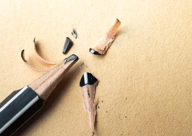 Lápis apontado sobre uma folha de papel velha vazia com uma ponta quebrada.