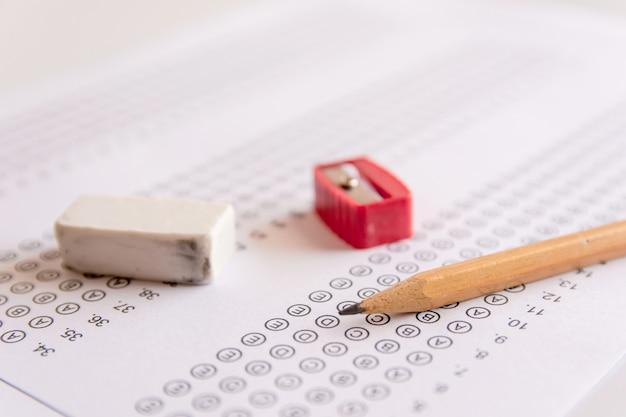Lápis, apontador e borracha em folhas de respostas ou formulário de teste padronizado