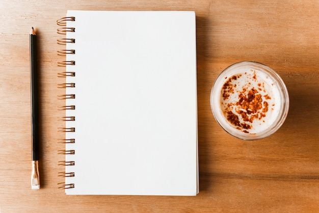 Lápis; bloco de notas em espiral e café em pano de fundo de madeira
