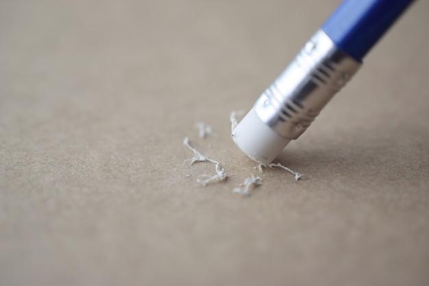 Lápis borracha, borracha de lápis, removendo um erro escrito em um papel marrom, excluir, corrigir e conceito de erro