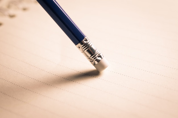 Lápis borracha removendo um erro escrito em um pedaço de papel, excluir, corrigir e conceito de erro.