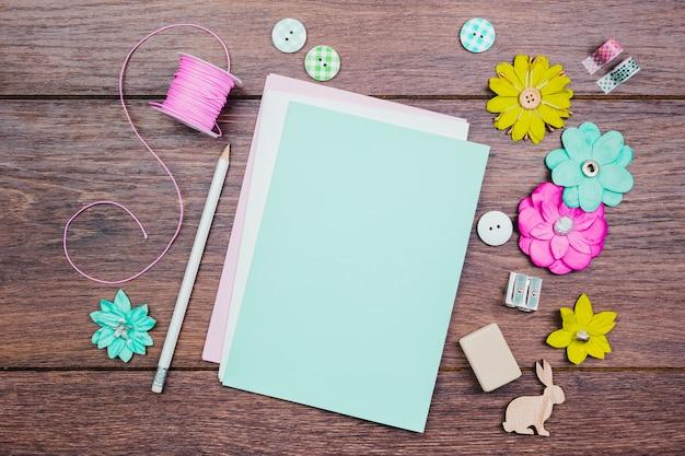 Lápis brancos; botões; flores coloridas e carretel rosa na mesa de madeira