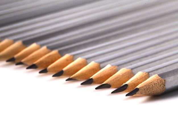 Lápis brilhante, destacando-se da multidão de muitos companheiros pretos idênticos na mesa branca. liderança, conceito de sucesso do negócio