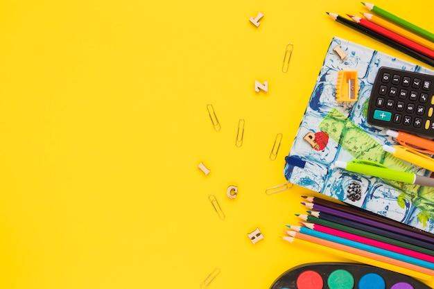 Lápis brilhantes e notebook colocado no lado direito