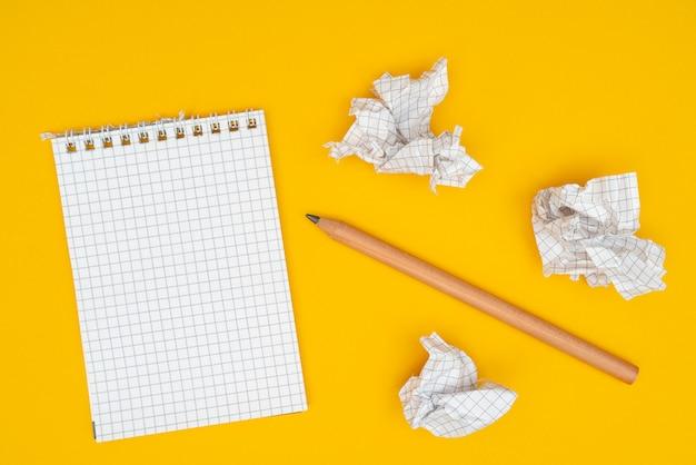 Lápis, caderno e folhas de papel amassado.