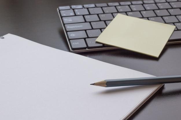 Lápis, caderno em uma mesa escura, ao lado do teclado