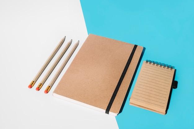 Lápis; caderno fechado e bloco de notas em espiral no pano de fundo branco e azul