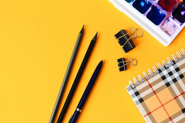 Lápis, caderno, tintas aquarela sobre um fundo amarelo claro. volta ao conceito de escola.