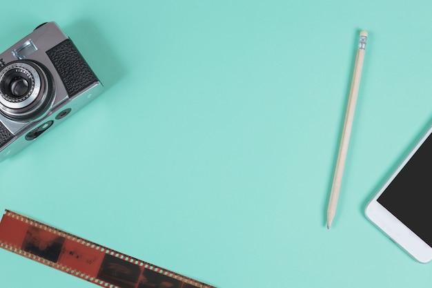 Lápis; celular; câmera e uma tira de filme antigo contra o fundo turquesa