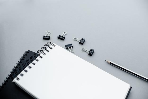 Lápis, clipes de papel e bloco de notas em um fundo abstrato cinzento