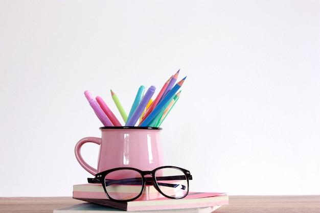 Lápis colorido cor e marcador em cima de livros e vidro
