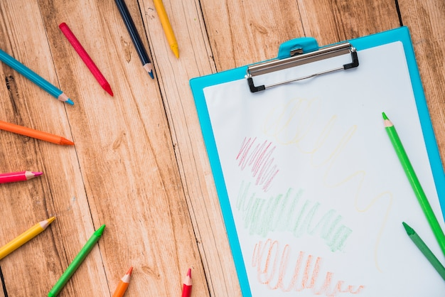 Lápis colorido e prancheta com papel branco na mesa de madeira