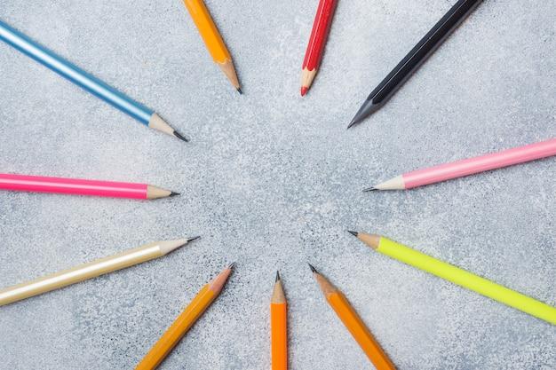Lápis coloridos brilhantes na tabela cinzenta. escola de conceito. espaço da cópia