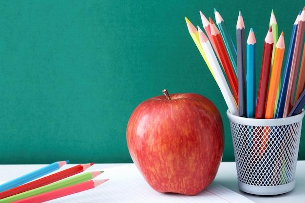 Lápis coloridos com apple em um bloco de notas