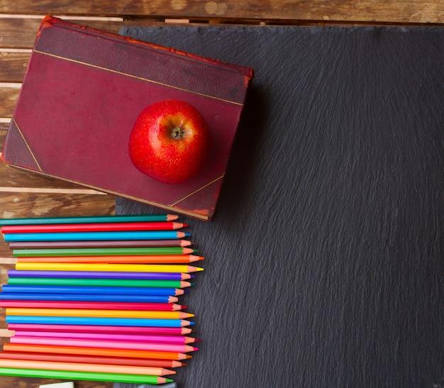 Lápis coloridos com livro velho e maçã vermelha no quadro preto