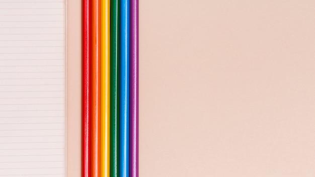 Lápis coloridos de arco-íris e notebook em fundo bege