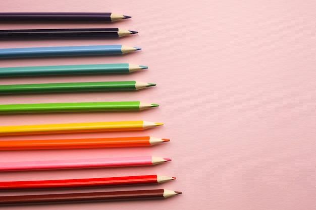 Lápis coloridos de cores do arco-íris no fundo rosa pastel com copyspace