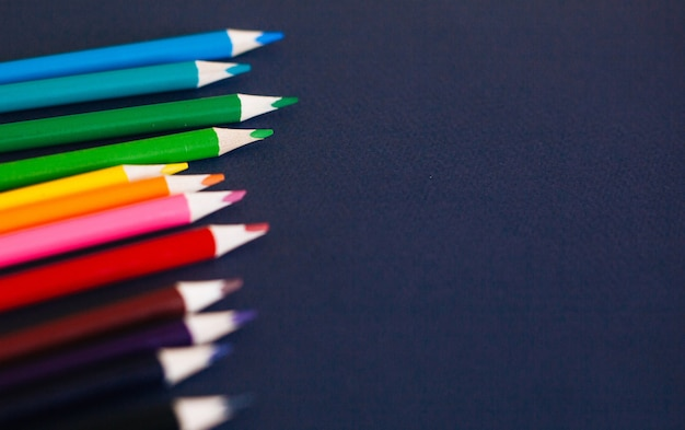 Lápis coloridos de encontro à obscuridade - fundo azul.