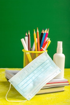 Lápis coloridos de frente com cadernos e spray na mesa amarela