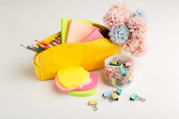 Lápis coloridos de frente com caixa de canetas e adesivos na mesa branca