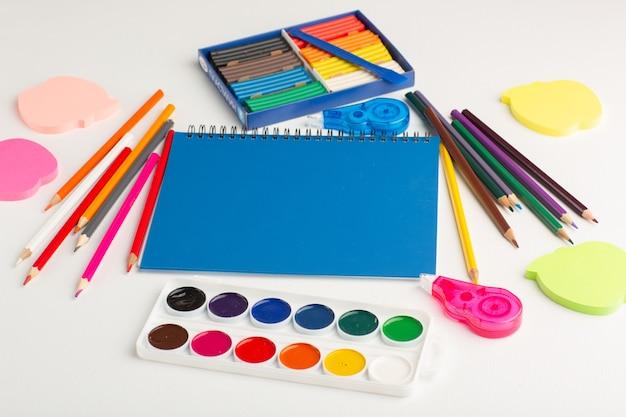Lápis coloridos de frente com tintas e adesivos em uma mesa branca clara