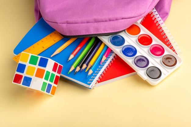 Lápis coloridos de frente com tintas para cadernos e bolsa roxa na mesa amarelo claro